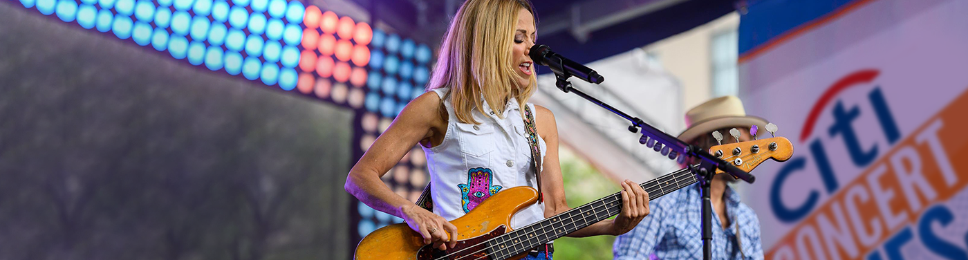 Sheryl Crow is singing on stage while playing a guitar.